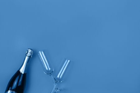 Champagne bottle and glasses on trendy blue background with place for text. Holiday concept. Flat lay style. Mockup for your web banner design. Фото со стока