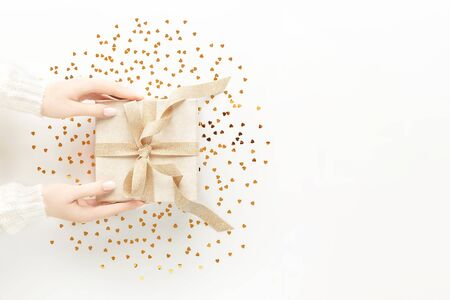 Female hands in warm white sweater with beautiful white manicure holding present box with elegant golden bow on white background with gold heart sheped sparkles. Festive backdrop for your holiday design. Flat lay style.