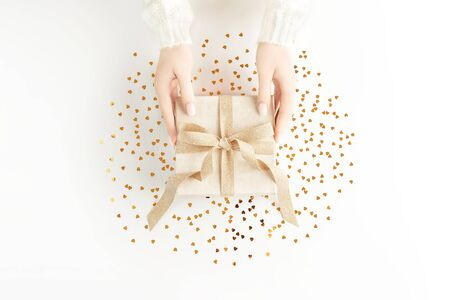 Female hands in warm white sweater with beautiful white manicure holding present box with elegant golden bow on white background with gold heart sheped sparkles. Festive backdrop for your holiday design. Flat lay style. Banque d'images - 138466431