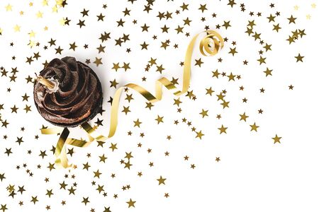 Delicious chocolate cupcake with chocolate icing, sprinkled gold sparkles and burning candles on white background with golden star shaped confetti and party streamer. Flat lay style. Holiday concept. Mockup for your design. Place for text.