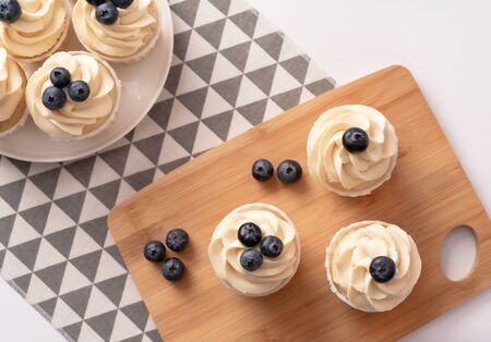 Homemade cupcakes with blueberry and vanilla cream on porcelain plate and wooden board. Flat lay style. Close-up.