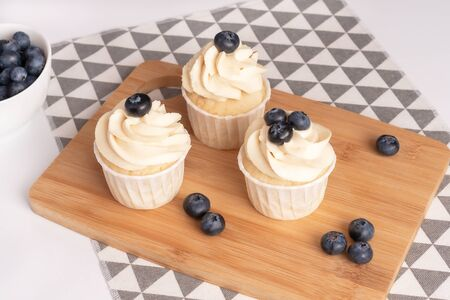 Homemade cupcakes with blueberry and vanilla cream on wooden board. Close-up.
