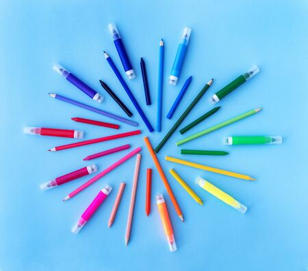 Back to school background with variety of pencils, markers and wax crayons in rainbow colors on pastel blue backdrop. Flat lay style. Place for text.