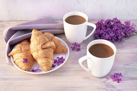 Two beautiful porcelain cups of coffee with milk with croissants decorated with lilac flowers on white wooden table. Perfect breakfast concept. Copy space.