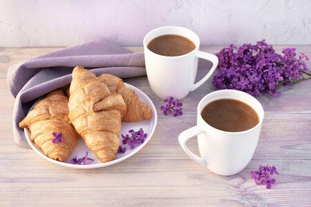 Deux belles tasses de café en porcelaine avec du lait avec des croissants décorés de fleurs lilas sur une table en bois blanc. Concept de petit-déjeuner parfait. Copiez l'espace.