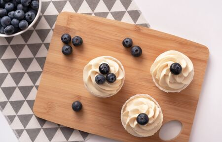Homemade cupcakes with blueberry and vanilla cream on wooden board. Flat lay style. Copy space.