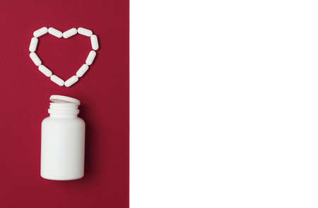 Mock-up bottle with spilled white pills in a shape of heart on red and isolated white background. Flat lay style. Copy space. Medicine, healthcare and pharmacy concept.