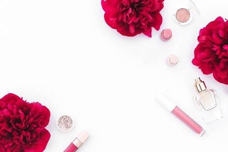Trendy design template with pink cosmetics layout decorated with wine red peonies on white background. Flat lay style. Copy space. Mockup for your design.