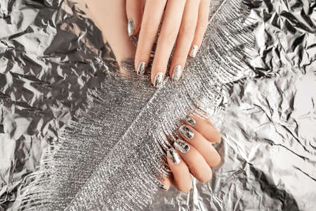 Female hands with trendy silver nail design on foil background holding Christmas decoration metallic feather. Festive backdrop for holidays. Flat lay style.