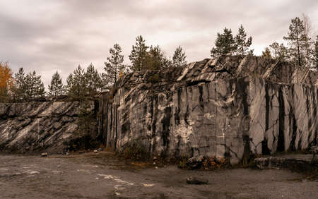 Picturesque natural park landscape with grey and white marble cliff and autumn forest. Dark and moody feel. Nature background.