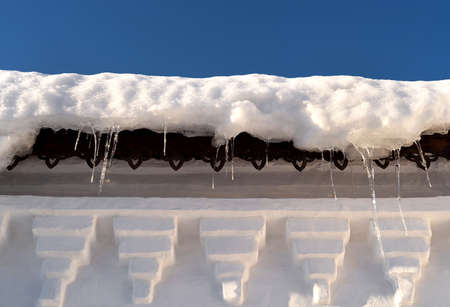 Beautiful background of white church roof fragment with icicles on winter day at sunset. Winter background. Reklamní fotografie