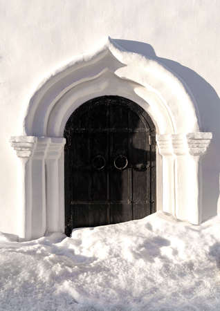 Beautiful background of white church fragment with iron wrought door on winter day at sunset. Winter background.