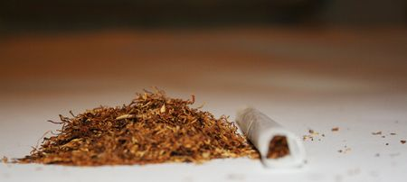 Heap of loose tobacco with hand rolled cigarette closeup