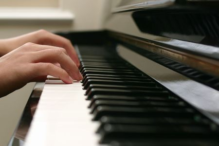 lesson: Close-up of hand playing the piano Stock Photo
