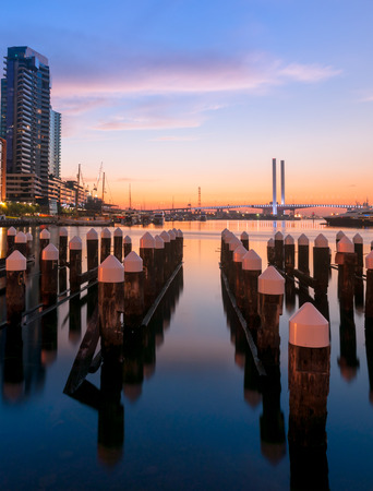 docklands: Long exposure shot of Colorful twilight of Bolte bridge and mooring poles at Docklands harbour of Melbourne