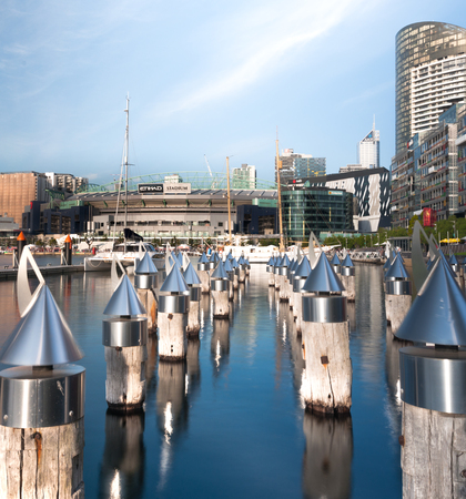 afl: Long exposure shot of Etihad stadium with sculptural mooring poles in Docklands marina of Melbourne Editorial