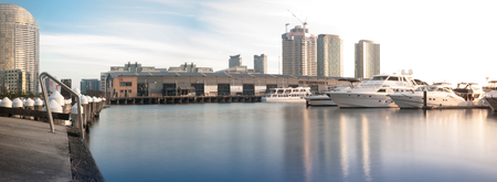 Long exposure shot of Shed 14 and many docked yachts with sculptural mooring poles in Docklands marina of Melbourne
