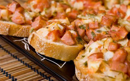worsten: Gebakken pizza broodjes op een zwarte plaat