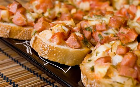Baked pizza sandwiches on a black plate