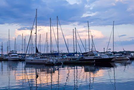 Docked sailboats in marina at sunset