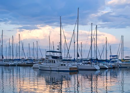Boats and yachts moored in harbor at sunset