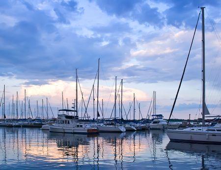 Jachten en boten afgemeerd in de haven bij zons ondergang  Stockfoto