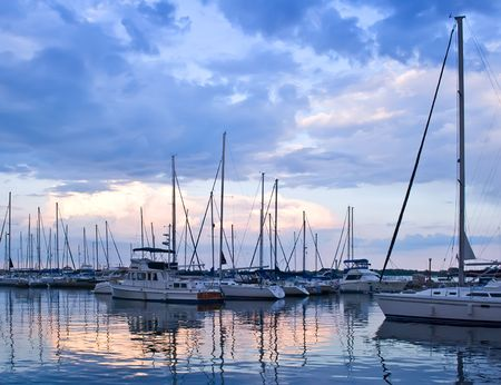 Yachts and boats moored in harbor at sunset Banque d'images
