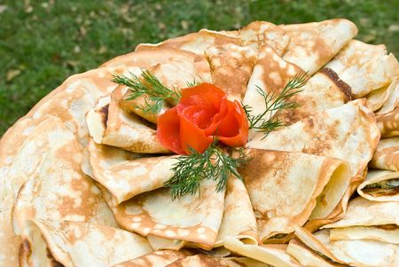 Pancakes stuffed with feta cheese and spinach and decorated with tomato rose and dill
