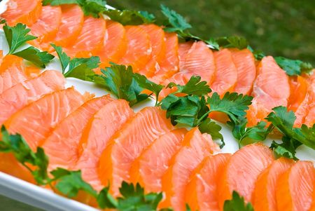 Sliced smoked salmon fillet decorated with green parsley on white plate
