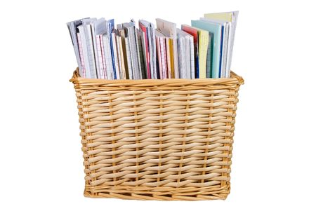 Straw colored wicker basket with textbooks, catalogs and papers