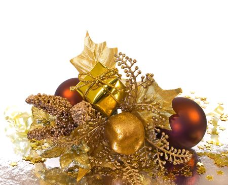 Christmas ornament - golden branch with baubles, gift box, leaves and other decorations Фото со стока