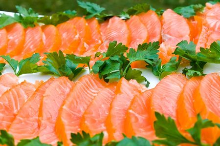 Smoked salmon fillet sliced and decorated with green parsley on white plate