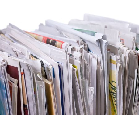 Vertical pile of newspapers and flyers on white background