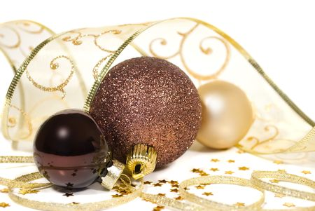 Three gold and bronze balls decorated with twisted ribbon garlands and stars - christmas decor Stock Photo