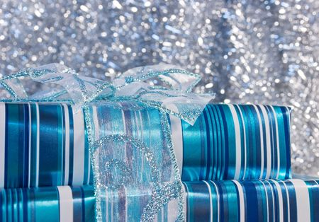 Blue glossy wrapped gift boxes decorated with a bow