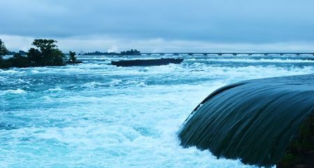 Splashing blue waters of the Niagara Falls before falling down at dusk Фото со стока