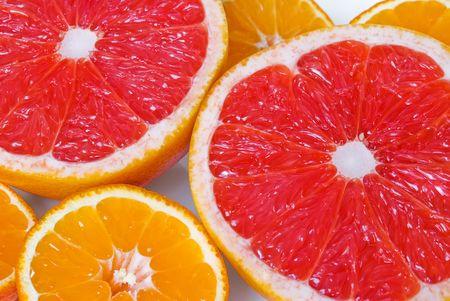 Pieces of pink grapefruits and mandarines Фото со стока