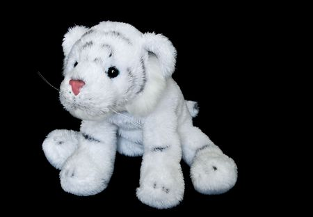 White with black striped tiger cub plush toy on black background