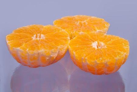 Bunch of half mandarins on blue lilac background Banque d'images
