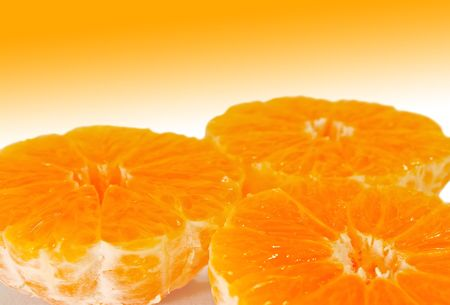 Three bright half mandarins without peel over white