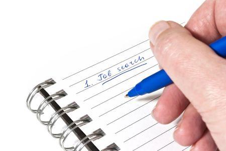 Writing down a job search plan on white paper photo