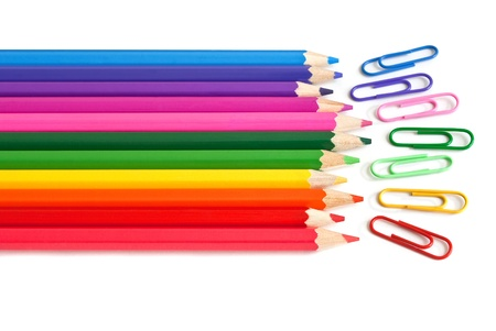 Colored crayons and paper clips, office stationery on white