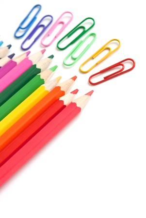 Row of color pencils and paperclips, office stationery on white
