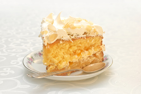 Piece of mango cake with white whipped cream and scattered almonds on top
