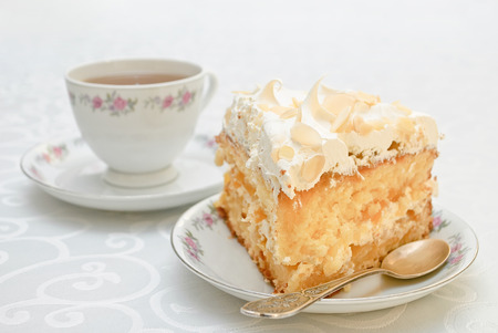 Piece of cake with white whipped cream and scattered almonds on top and a cup of tea