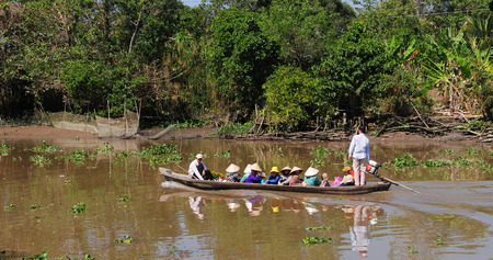 MEKONG DELTA, VIETNAM - JULY 20, 2014. Group of people sitting on motor boat, moving on canal, reflect on surface water, green tree at river, peaceful country, Vietnam.
