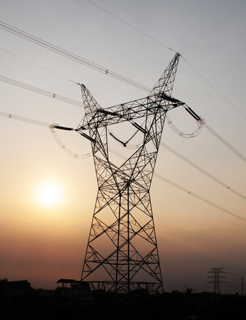 torres el�ctricas: Sun silhouetted detr�s de un establecimiento de torres de electricidad  Foto de archivo