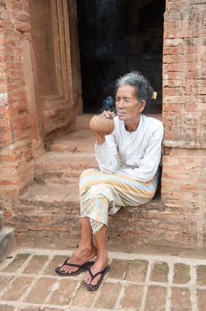 cheroot: Bagan, Myanmar, March 26, 2014. Asiatic old woman smoking a big handmade cigar in Bagan, Myanmar.