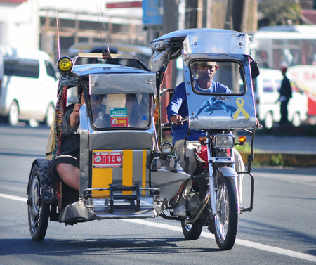 BORACAY, PHILIPPINES - MARCH 1, 2015. Tricycle on the street, Boracay, Philippines. Motorized tricycles are a common means of passenger transport everywhere in the Philippines.