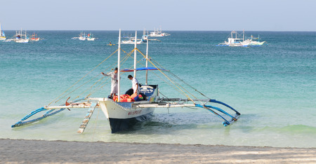 Boracay, Philippines - Feb 1, 2015. Tourists and traditional boat at White beach, Boracay Island, Philippines.